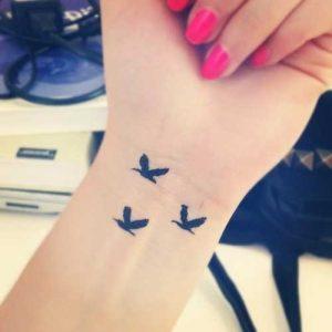minimalist swallow tattoo on wrist